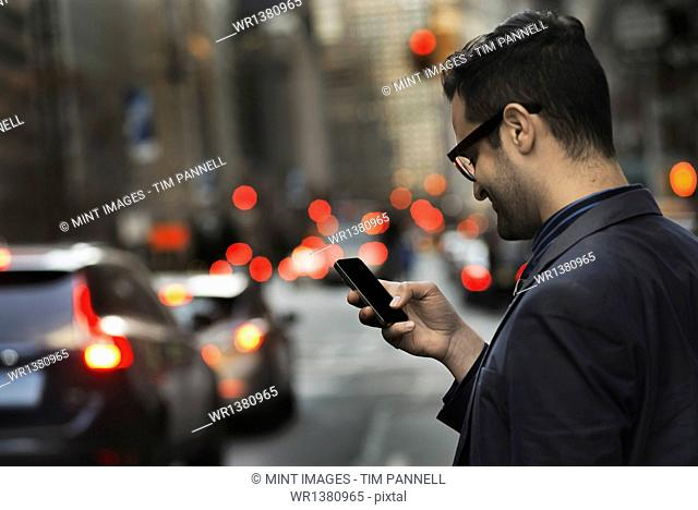 A man in a dark jacket checking his cell phone, standing on a busy street at dusk