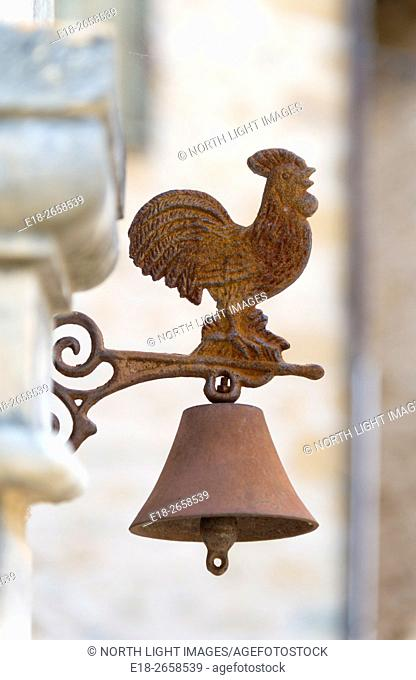 EU, France, Midi-Pyrénées, Carennac. Rusted metal, rooster topped doorbell on outside wall of home in quaint Dordogne Valley town