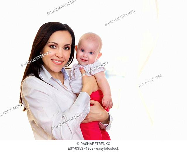 Happy smiling mother with six month old baby girl indoor