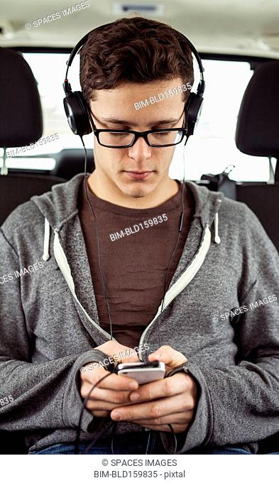 Caucasian man listening to mp3 player in car
