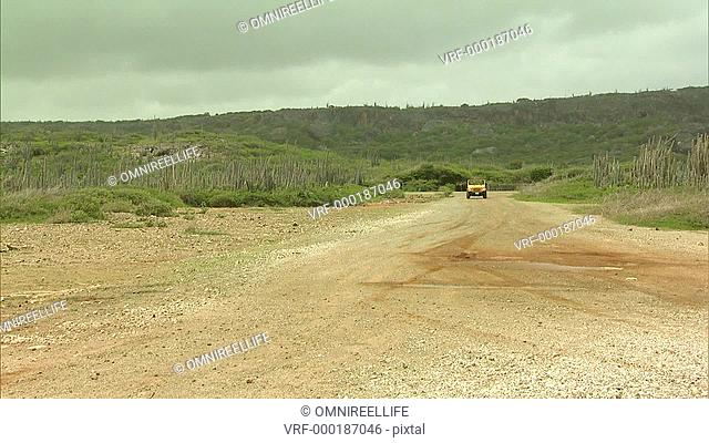 Two yellow jeeps driving along gravel road and stopping in front of the sea