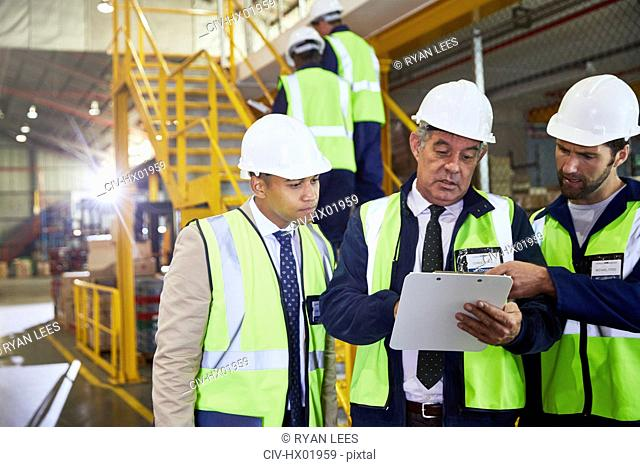 Manager and workers with clipboard meeting in distribution warehouse