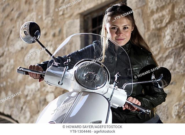 Girl sitting on a motor scooter
