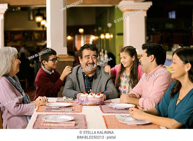 Family celebrating birthday or older man in restaurant