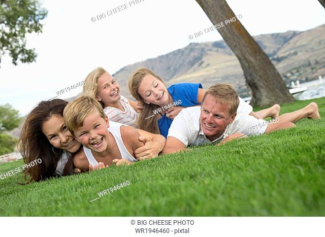 Portrait of a family of five in a dog pile near a lake