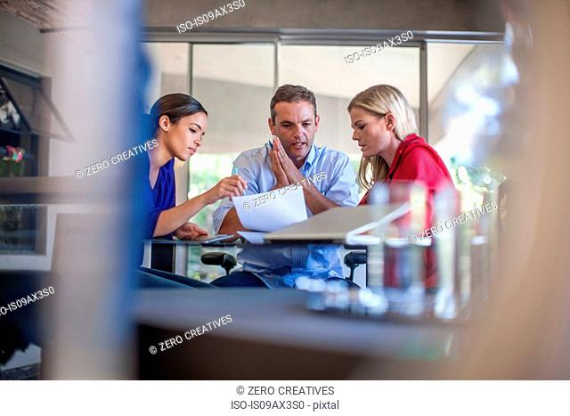 Three designers meeting at conference table in design office