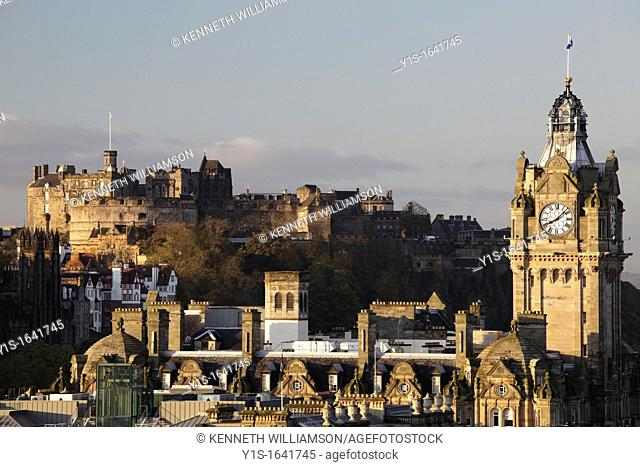 Looking across the Edinburgh skyline to the Castle with the Balmoral Hotel Clock Tower in the foreground at dawn Scotland UK