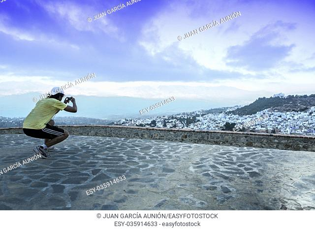 Sportsman observing a panoramic view of blue city of Chefchaouen at rising, Morocco