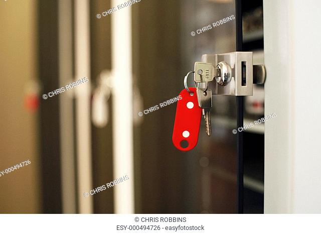 Keys with red keychain in lock close-up
