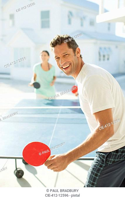 Couple playing table tennis outdoors