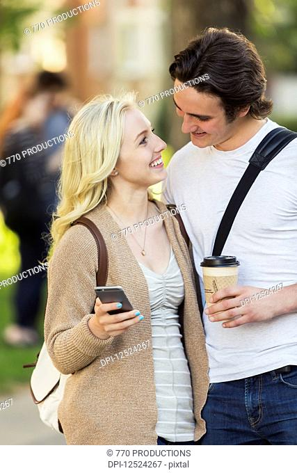 A young couple looking into each other's eyes and checking social media on a smart phone while walking through a university campus; Edmonton, Alberta, Canada