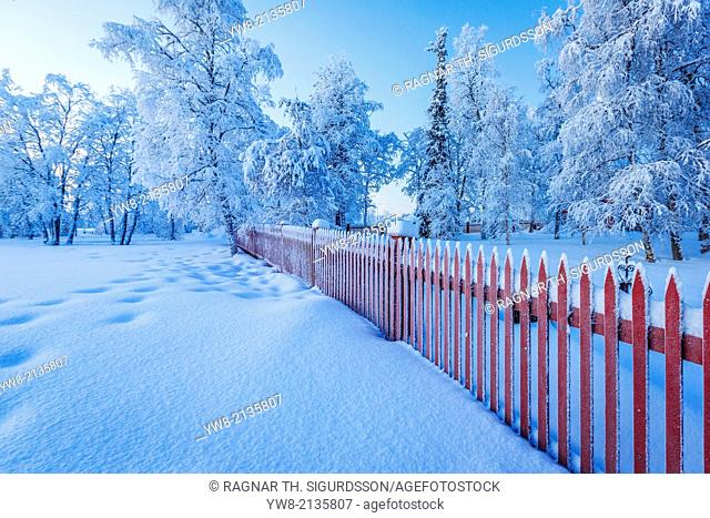 Red wooden fence, Wintertime, Jukkasjarvi, Lapland, Sweden. Cold temperatures as low as -47 celsius