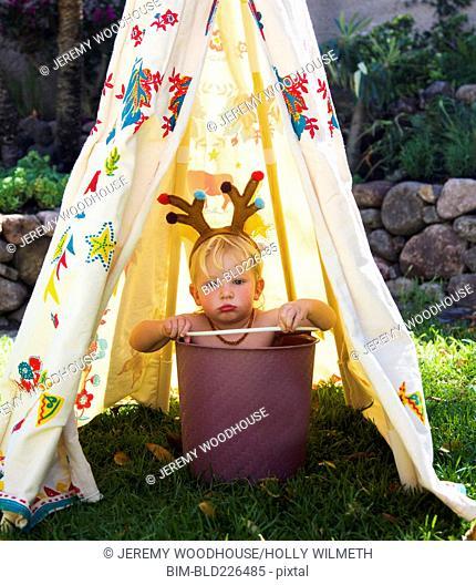 Pouting baby boy wearing antlers in bucket inside teepee