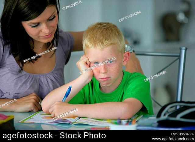 Portrait of a boy doing homework about a woman