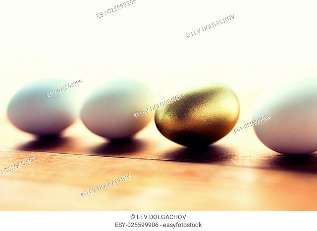 easter, holidays, tradition and object concept - close up of golden and white easter eggs on wood
