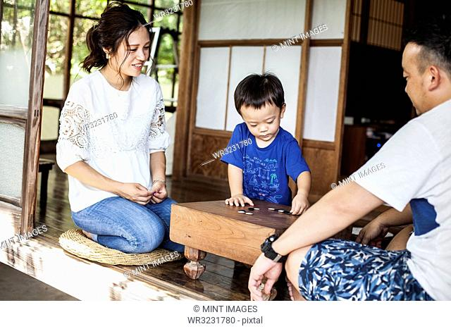Japanese woman, man and little boy sitting on floor on porch of traditional Japanese house, playing Go