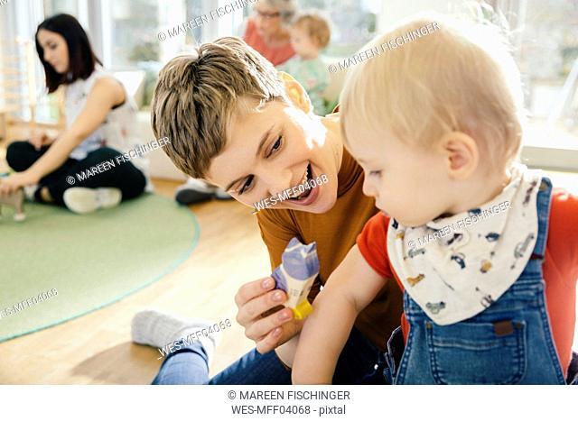 Pre-school teacher playing with toddler in kindergarten