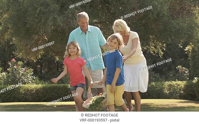 Grandparents and grandchildren walking in garden with basket of vegetables