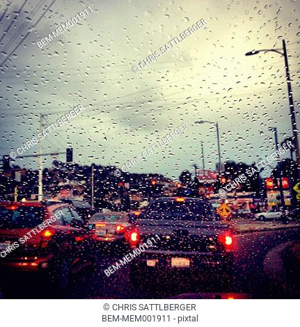 Traffic through rainy car windshield