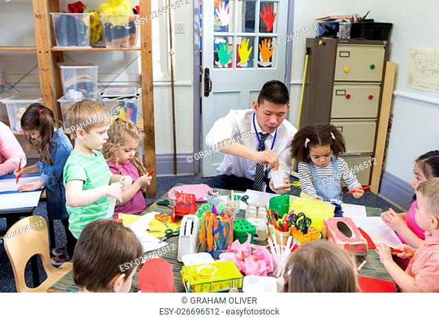Male teacher with a class full of nursery students. They are all sat at tables using arts and crafts