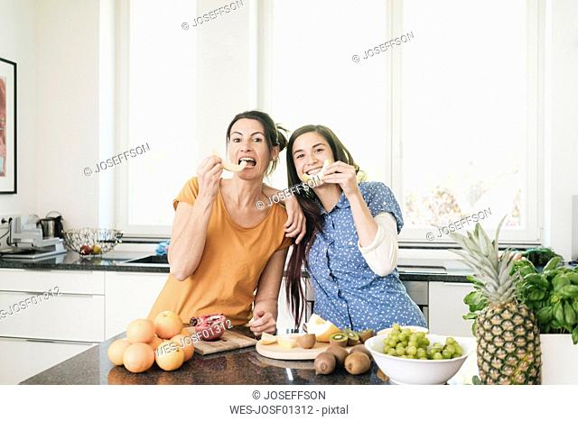Mother and adult daughter having fun together in the kitchen