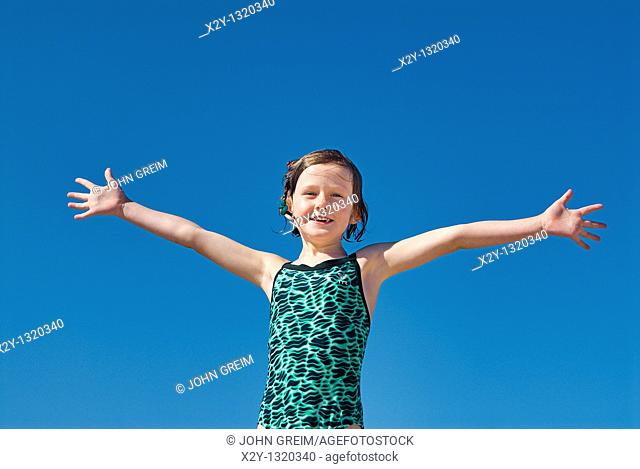 Joyous girl in bathing suit and open arms at the beach