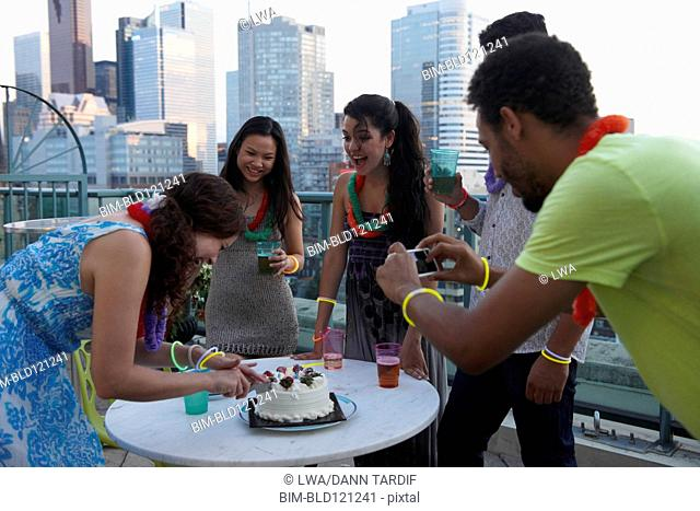 Friends celebrating birthday on urban rooftop