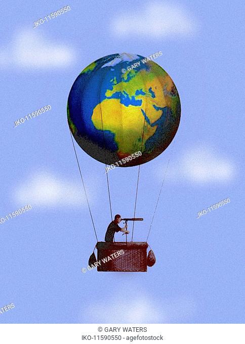 Man looking through telescope in globe hot air balloon