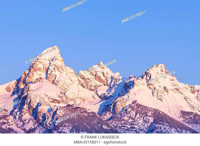 USA, Wyoming, Grand Teton National Park, snow-covered mountaintops at sunrise