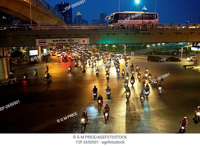 pack of motorcycles crosses intersection on Rama IV road at dusk, Bangkok