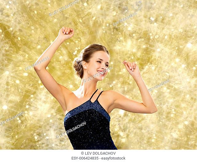 people, party, holidays and glamour concept - smiling woman dancing with raised hands over yellow lights background