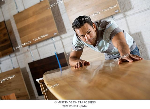 A young man in a workshop which uses recycled and reclaimed lumber to create furniture and objects