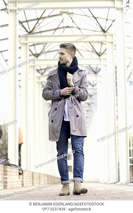 man wearing coat and scarf, in city Munich, Germany