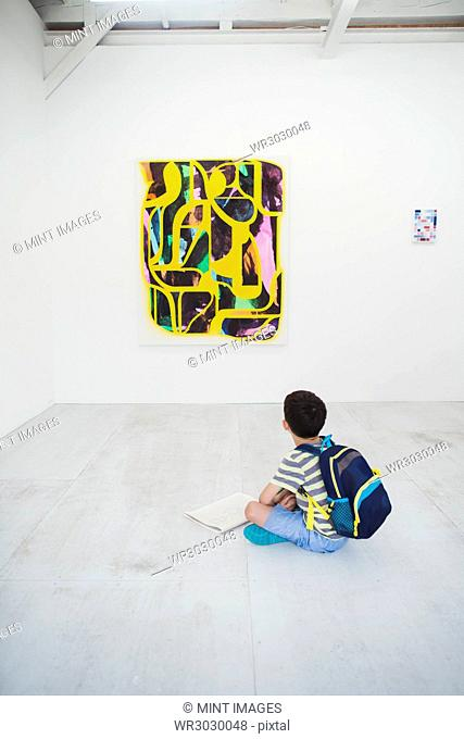 Boy with short black hair wearing backpack sitting on floor in art gallery with pen and paper, looking at modern painting