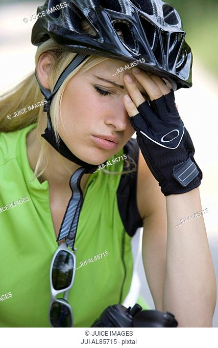 Close up of woman in biking gear with headache