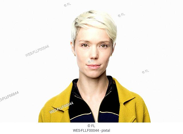Portrait of woman with short blond dyed hair in front of white background
