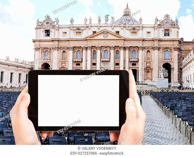 travel concept - tourist photographs St Peter square and Basilica in Vatican city on tablet with cut out screen with blank place for advertising in Italy