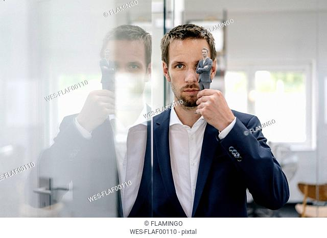 Businessman holding his 3D portrait in front of his eye