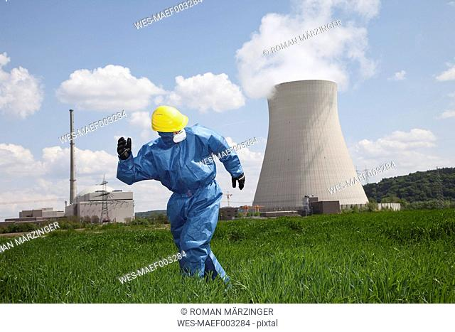 Germany, Bavaria, Unterahrain, Man with protective workwear running in field at AKW Isar