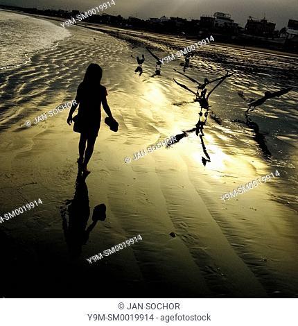 A girl walks on the low-tide beach at the sunrise in Manta, Ecuador, 20 November 2014