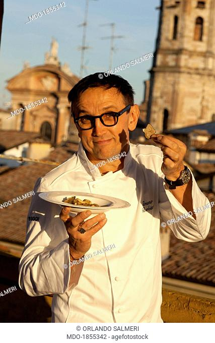 Italian chef awarded with many Michelin stars and judge at the show broadcasted by SkyUno 'Masterchef Italia' Bruno Barbieri showing proudly the dish of...