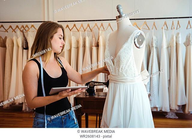 Female fashion designer adjusting the dress on mannequin