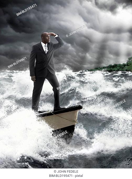 African American businessman standing at helm of boat on stormy sea