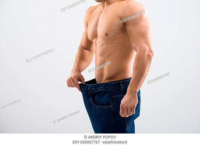 Midsection of muscular man in old jeans showing weight loss against white background