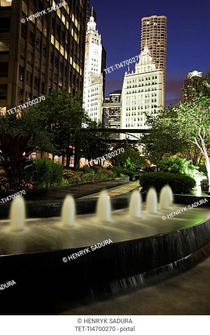 USA, Illinois, Chicago, Fountain and Wrigley Building illuminated at night