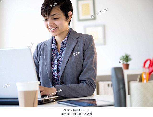 Mixed race businesswoman working on laptop computer at office desk