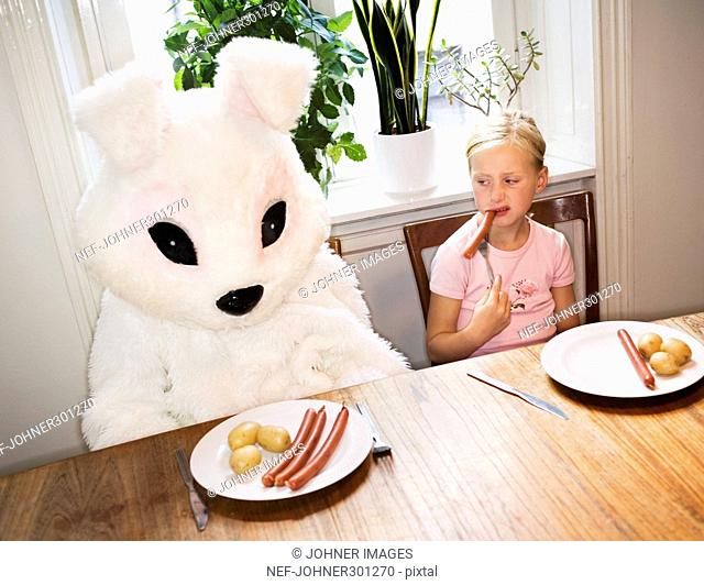A girl and a person in a bunny costume eating sausages