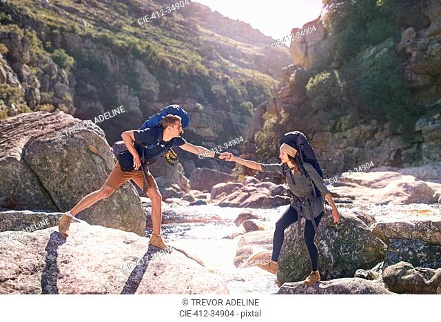 Young man helping girlfriend hiking, crossing sunny rocks in stream