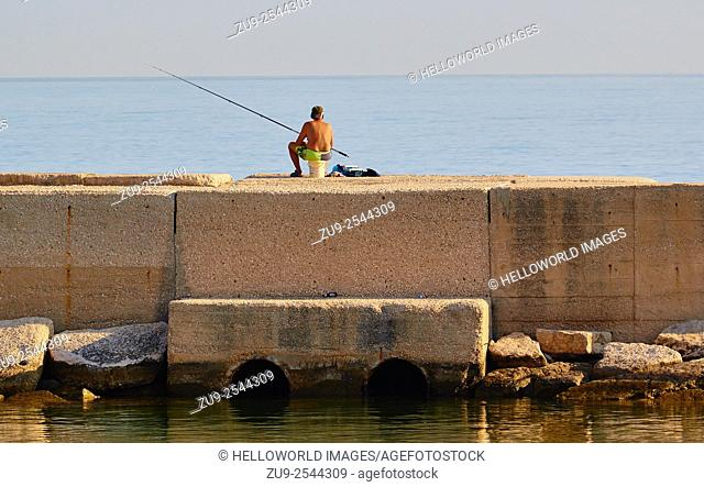 Man fishing from pier, Molfetta, Puglia, Italy, Europe