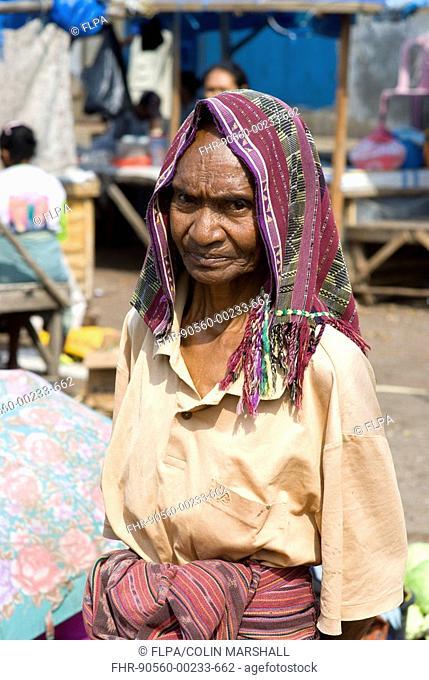 Old woman standing in market, Kalabahi, Alor Island, Alor Archipelago, Lesser Sunda Islands, Indonesia